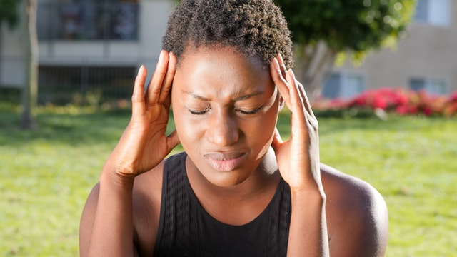 Brain Fog can show up with headaches, muscle tension, and the struggle to think clearly or focus. Image is a woman pressing her head to alleviate the pain from a headache.